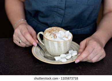 Female hands holding a cup with cappuccino and marshmallows