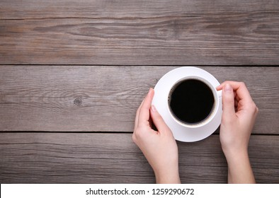 Female hands holding cup of coffee on grey wooden background.