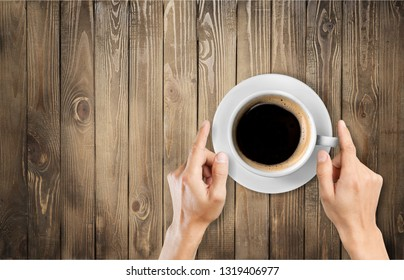 Female hands holding cup of coffee on grey wooden background.          - Image