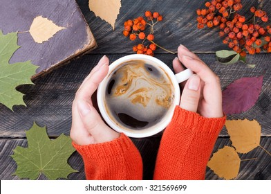 Female hands holding cup of coffee on autumn wooden background. Old book, autumn leaves and dried rowan on background. Concept cozy coffee cup. Top view