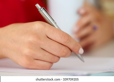 Female hands holding cup of coffee or tea and silver pen closeup. Woman writing letter, list, plan, making notes, doing homework. Student studying. Education, self development and perfection concept