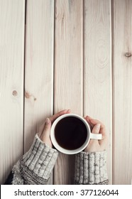 Female hands holding cup of coffee on rustic wooden table background.
