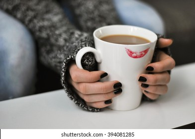 Female hands holding a cup of coffee with a lipstick mark