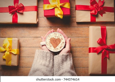 Female hands holding cup of coffee with Christmas gift boxes around on wooden table. Personal point of view