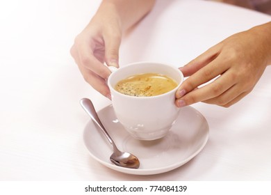 Female hands holding a cup of coffee, drink