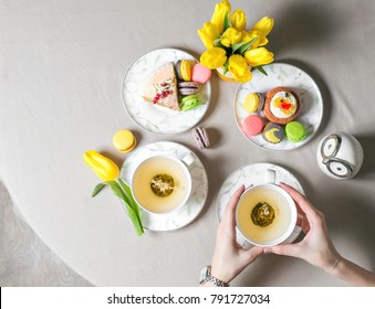 Female hands holding cup of green tea. top view. Beautiful morning in home. A lot of cake and desserts. Copy space