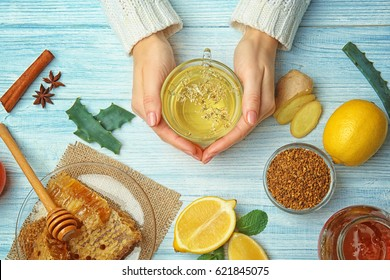 Female hands holding cup of herbal tea on wooden background