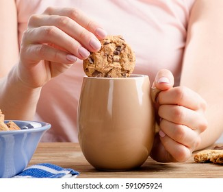 Female hands holding cup of tea and cookie. Selective focus