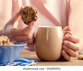 Female hands holding cup of tea and cookies. Selective focus