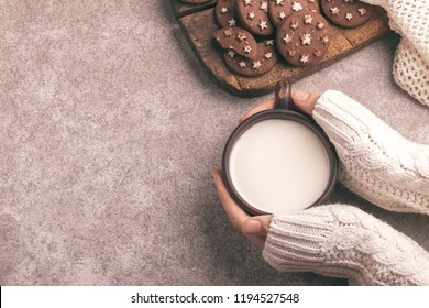 Female hands are holding cup of warm milk, chocolate cookies on the old wooden cutting board. Gray slate background. Top view. Cozy evening. Copy spase