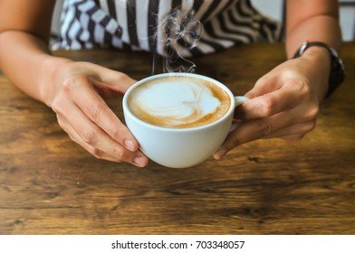 Female hands holding cups of hot coffee on rustic wooden table background