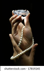 Female hands holding diamond and pearls