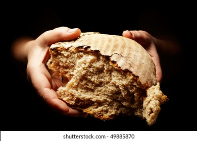 female hands holding a divided brown loaf of bread