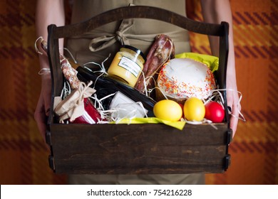 Female hands holding easter basket with colorful easter eggs, cake, red wine, hamon or jerky and dry smoked sausage. Food gift set for celebrating Easter
