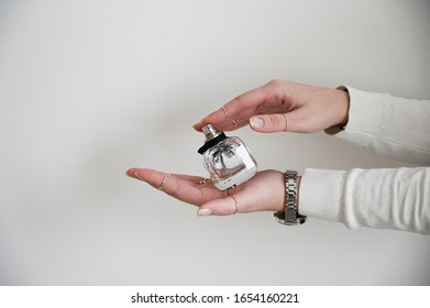 Female hands holding an empty bottle of fragrance. Designer piece. White background and details on hands. Girl wearing a cozy sweater. Perfume workshop banner.
