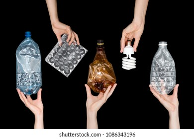 Female hands holding empty crushed plastic waste, lamp isolated on black background. Recyclable waste. Recycling, reuse, garbage disposal, resources, environment and ecology concept.