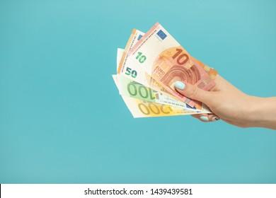 Female hands holding euro banknotes on a blue background. Euro Money. euro cash background