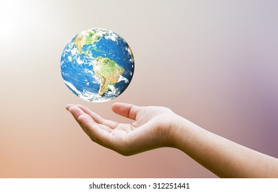Female hands holding floating earth on blurred sunset background with sun light. Elements of this image furnished by NASA