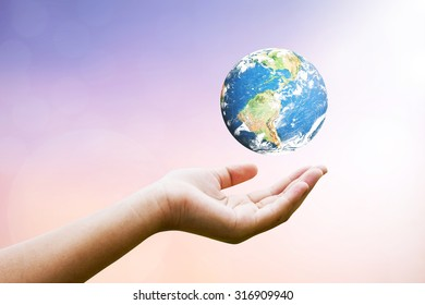 Female hands holding floating earth : blurred sunset background with sun light : Elements of this image furnished by NASA