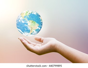 Female hands holding floating earth on pastel blur heaven clouds sky sunset background. Soft focus blue sky white sunlight day time. Open view out windows. Elements of this image furnished by NASA