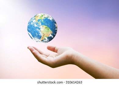 Female hands holding floating world on blurred sunset background with sun light : Elements of this image furnished by NASA