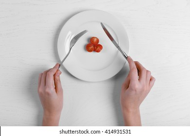 Female hands holding fork and knife on a plate with cherry tomatoes on white table.