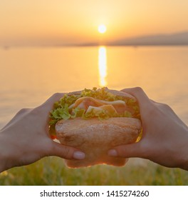 Female hands holding fresh burger in front of sea at summer sunset, point of view.