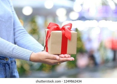 Female hands holding gift box with red ribbon for Christmas and New Year's Day or Greeting season, Valentines day
