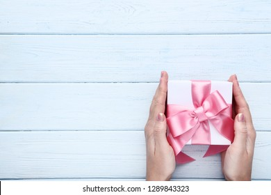 Female hands holding gift box with ribbon on wooden table