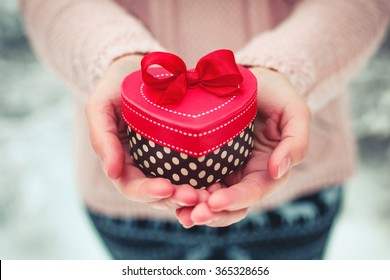 Female hands holding a gift box shaped of heart. Saint Valentine's day concept. Toned picture