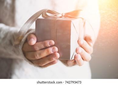 Nainen kädet kädessä lahjapakkauksessa. Kopioi tilaa. Joulu, hew vuosi, syntymäpäiväkonsepti. Juhlava tausta bokeh ja auringonvalo. Magic satu
