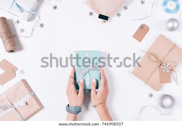 Female hands holding a gift box with ribbon among Christmas decorations and snowflakes on a white table top view