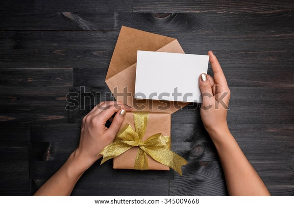 Female hands holding gift card and gift box over the black wooden table
