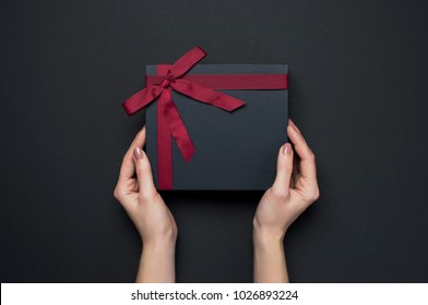 Female hands holding a gift with a red ribbon, one object on a dark background. Gift holiday. Festive background. Top View Flat Lay Advent Gift