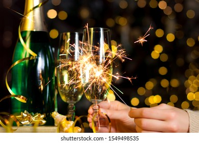 Female hands are holding glass with champagne, burning sparkle. Gold decor, balls, serpentine on table. Decorative garland with yellow light bulbs are shining on background. New year, christmas mood.