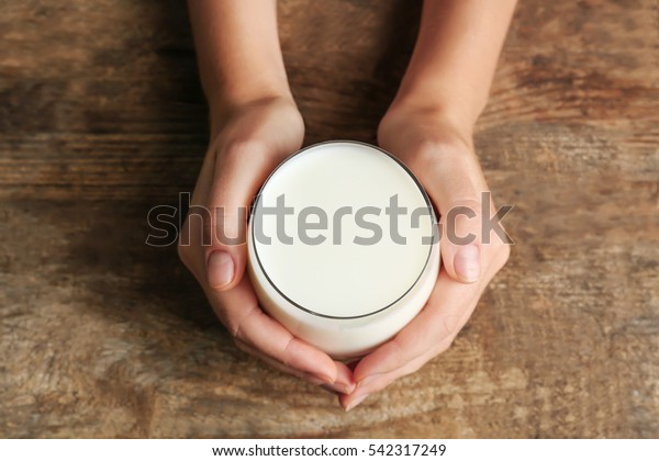 Female hands holding glass of milk on blurred wooden background, closeup