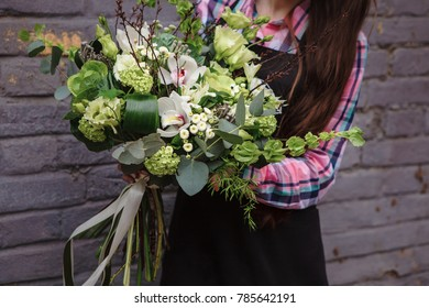 female hands holding green bouquet of Bronica, Brassica, Orchid, eustoma, hydrangea