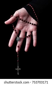 Female hands holding and hanging a rosary with Jesus Christ in cross or Crucifix on black background. Woman with Christian Catholic religious faith