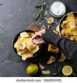 Female hands holding home made potato chips served with mustard, rosemary, fleur de sel salt, lemon on stone background. Top view. Copy space. Square image