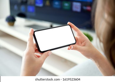 female hands holding horizontally phone with isolated screen on the background of TV in the room - Shutterstock ID 1619523604