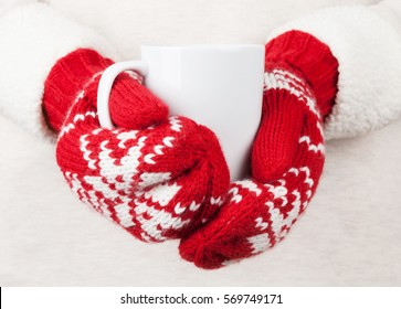 Female hands holding hot chocolate in red mittens