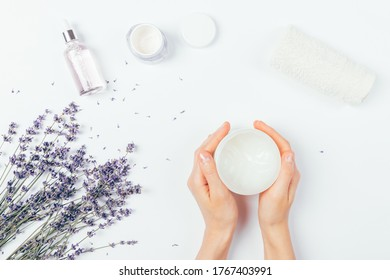 Female hands holding jar of cosmetic cream next to lavender flowers, aromatic oil and towel on white table, top view.