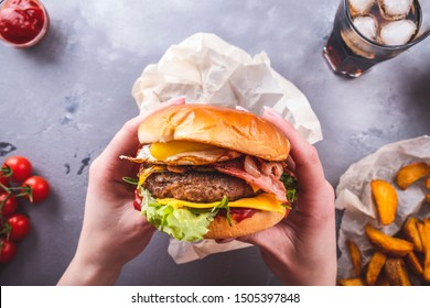 Weibliche Hände, die einen saftigen Rindfleischburger halten. Amerikanisches Fastfood. Draufsicht