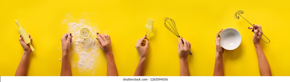 Female hands holding kitchen tools, sieve, rolling pin, bowl, sieve, brush, whisk, spatula for baking and cooking over yellow background. Food frame, bake concept with copy space.