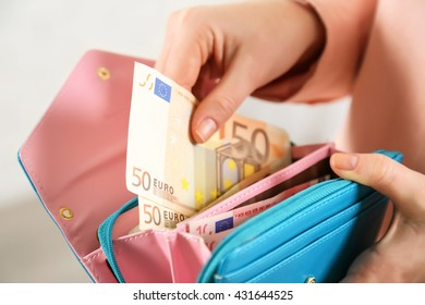 Female hands holding leather purse with euro banknotes closeup