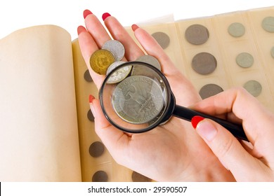 The female hands holding a magnifier and coins from an album of the collector of coins