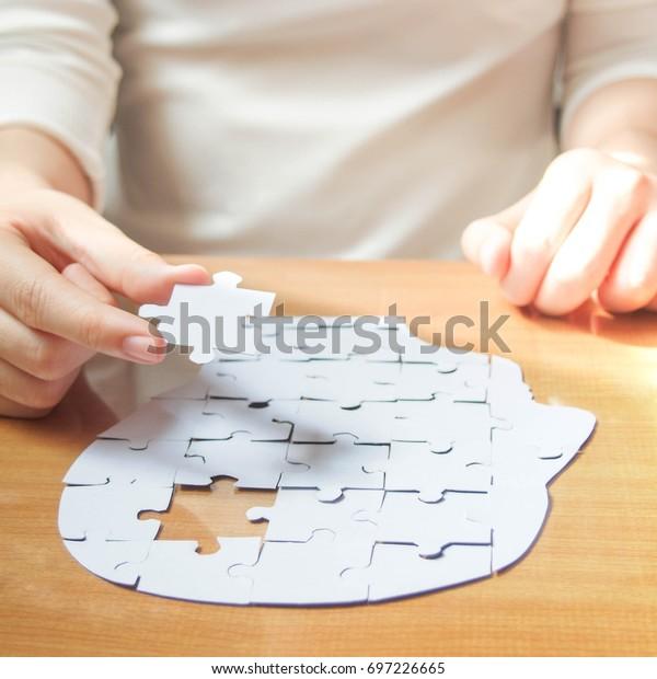 Weibliche Hände, die fehlende weiße Puzzleteile in der Form eines menschlichen Kopfgehirns halten. Kreative Idee für Gedächtnisverlust, Demenz, Alzheimer-Krankheit und Konzept für geistige Gesundheit. Platz.