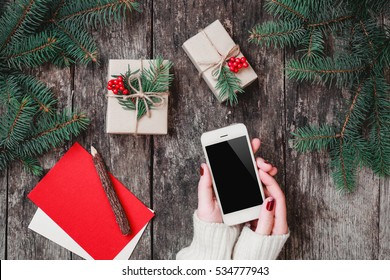 Female hands holding mobile phone on wooden background with Christmas gifts, Fir branches. Xmas and Happy New Year composition. Flat lay, top view