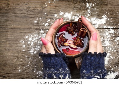 Female hands holding mug with mulled wine above wooden table. Top view