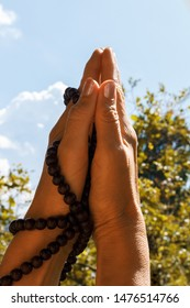 female hands holding namaste mudra with Mala Beads Bracelet during woman's morning practice. folded hands reach for the sky and the sun, vertical image